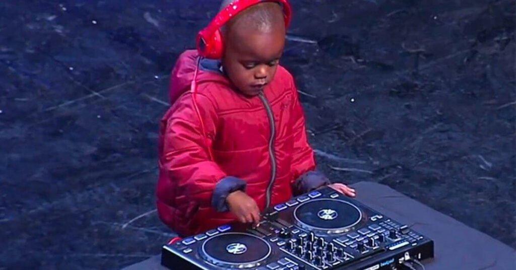 Een klein kind met rode jas achter een DJ set