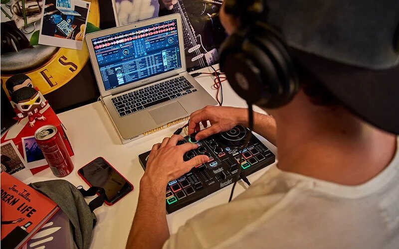 Een student thuis aan het mixen op een Hercules DJ controller