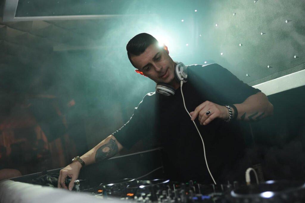 Een DJ die draait op een feest met wit licht